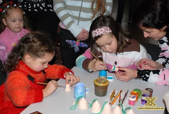 Діти разом з батьками розписують дзвіночки під керівництвом Наталі та Людмили Дворяківських