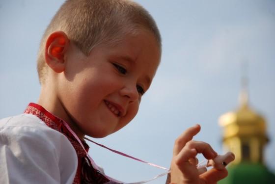 Хлопчик на руках у батька зачарований свищиком