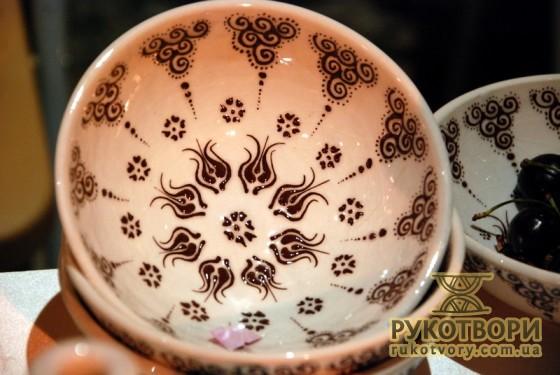 На тарілці зображена організація світу, по центру якого зображений Бог у вигляді квітки.